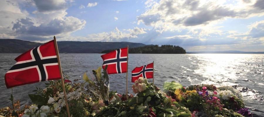Norwegian flags and flowers are seen in Sundvollen, close to Utoya island, background, where gunman Anders Behring Breivik killed at least 68 people, near Oslo, Norway, Thursday July 28, 2011. (AP Photo/Lefteris Pitarakis)